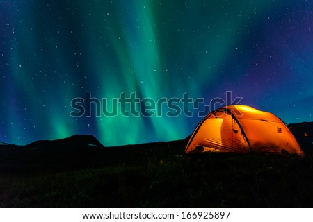 illuminated Tent and northern lights - stock photo