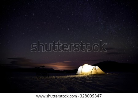 illuminated tent at night in sweden in the winter time with Aurora borealis - stock photo