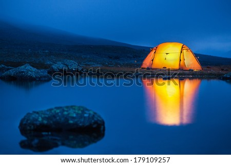 illuminated tent on a lake with reflexions in the blue hour - stock photo
