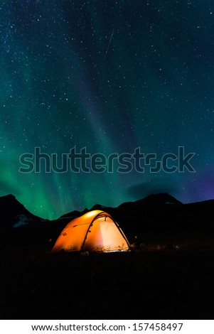 Illuminated Tent with northern Lights - stock photo