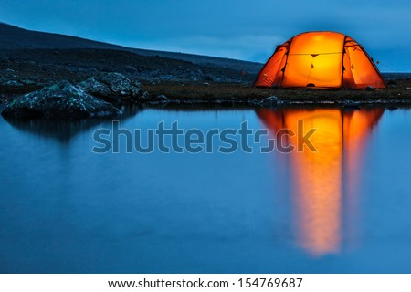 Illuminated Tent with reflection - stock photo