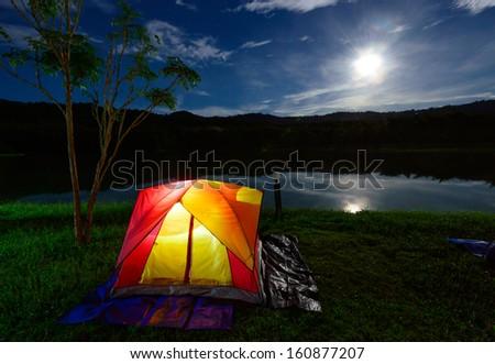 Illuminated Yellow Red Camping tent at Night - stock photo