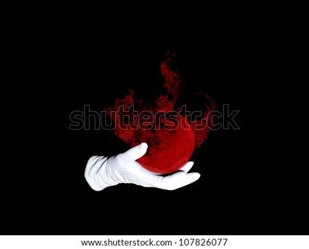Illusionist holds burning planet on the black background - stock photo