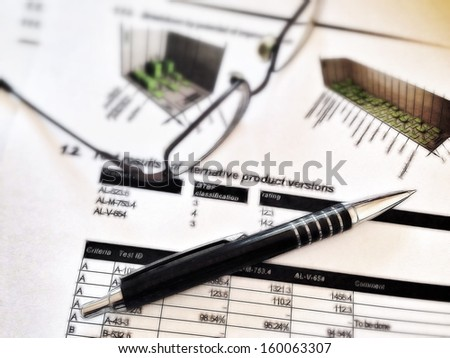 Illustrated pen and glasses laying on a report with statistics, referring to concepts such as corporate reporting, scientific studies, professional occupations, business and project management - stock photo