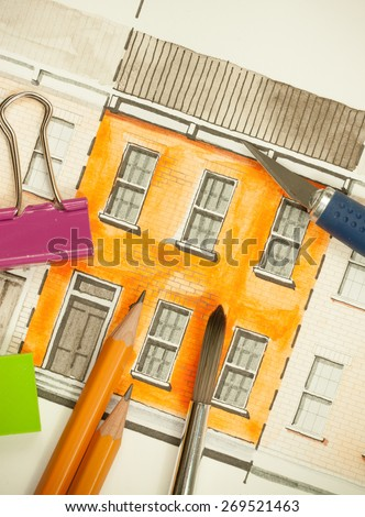 Illustration graphic material with orange shared twin elevation facade fragment with brick wall texture tiling shot with brush, pencils and cutting tool, symbolizing custom approach to building design - stock photo