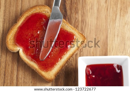 Illustration of raspberry jam sandwich with bread knife on a wooden background - stock photo