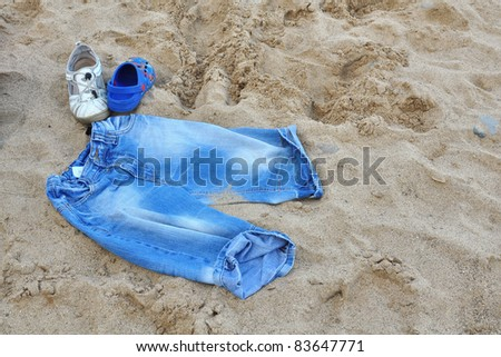 Illustration of summertime vacation, with jeans shorts and two sandals on beach sand. - stock photo