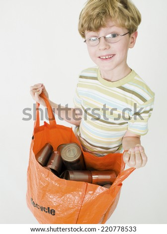 illustrative shot of young boy holding bag of tin cans for recycling on white background - stock photo