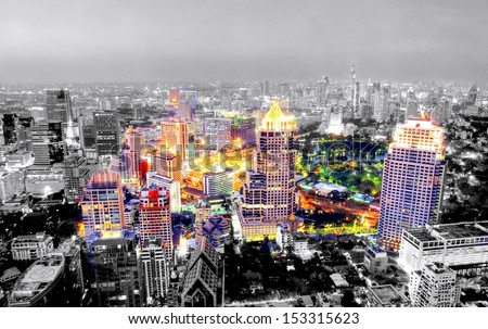Image in black and white with selective color from the asian city of Bangkok , Thailand at nighttime when the tall skyscrapers are illuminated - stock photo