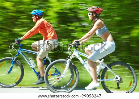 Image in motion of two bicyclists riding down country road - stock photo