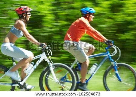 Image in motion of two bicyclists riding on country road - stock photo