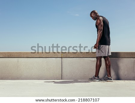 Image muscular young man on a walkway getting ready for his run. Focused male athlete preparing for his running workout outdoors against sky with copy space.  - stock photo