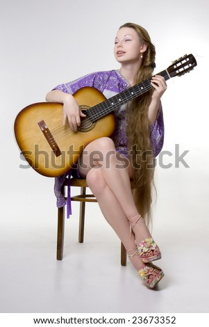 Image of a beautiful girl who plays the guitar - stock photo