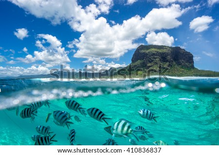Image of a beautiful mountain and clouds from the ocean.Ã?? The lower part of the picture - the underwater world with fishes - stock photo