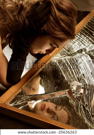 image of a beautiful woman in a  broken mirror - stock photo