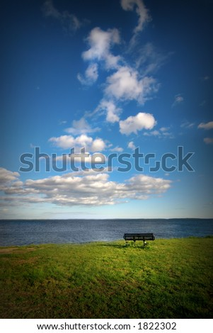 Image of a bench facing the ocean on a warm summer afternoon. It's just you and the ocean. Themes: meditation, wellness, maybe retirement. - stock photo