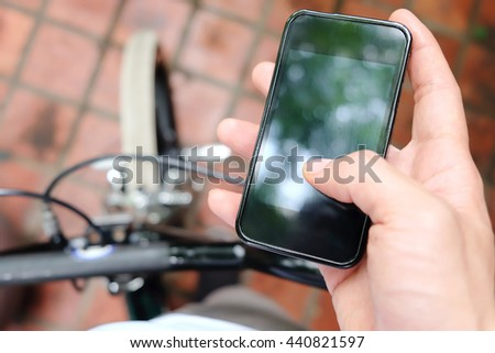 image of a biker texting on a smart phone - stock photo