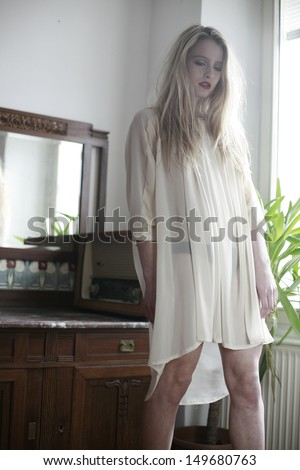 image of a bond beautiful girl by the window, a delicate blonde girl, girl in transparent dress, fogy morning light  - stock photo