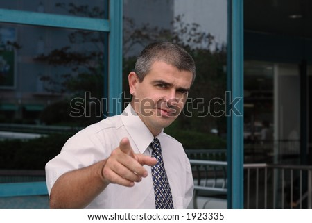 Image of a business leader giving working indications to his team in a city. Selective focus on the man, the background and the hand are blurred. - stock photo