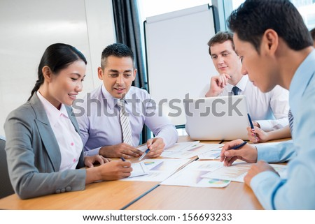 Image of a business team working at the project together on the foreground - stock photo