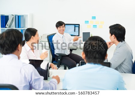Image of a businessman presenting something at the seminar using tablet at the office on the foreground - stock photo