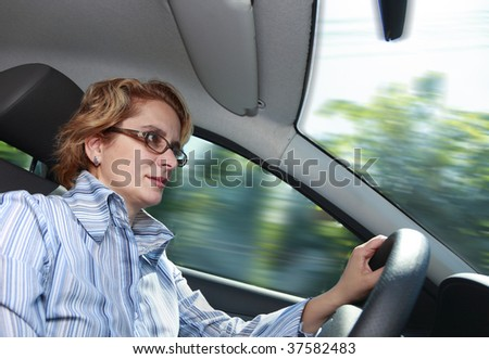 Image of a businesswoman driving a car. - stock photo
