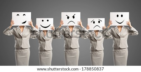 image of a businesswomen standing in a row, held in front of a plate with signs - stock photo