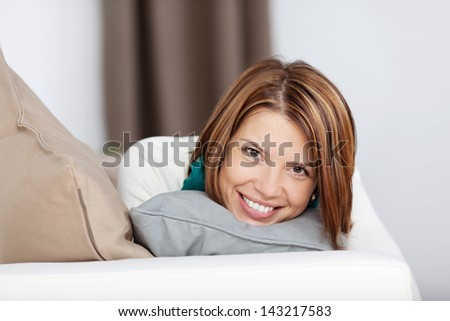 Image of a cheerful young woman hugging the pillow while lying on the sofa and giving a beautiful smile. - stock photo