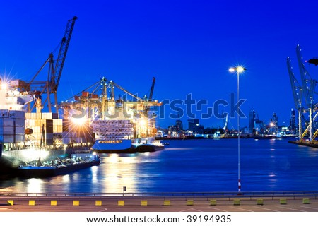 Image of a city port with intense blue saturated color. Boats are on the water, and the city of Rotterdam is viewable in the background. No people. Horizontally framed shot. - stock photo