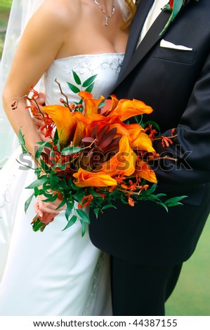 Image of a colorful bouquet being held by a bride and groom - stock photo