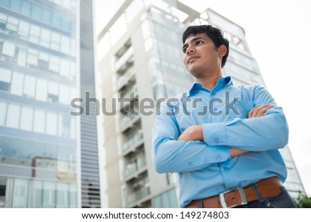 Image of a confident young man standing in the city with his arms crossed - stock photo