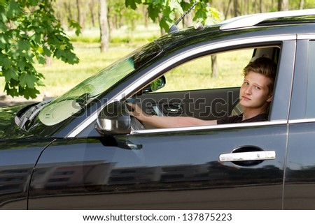 Image of a cute young boy driving a black car and posing for the camera while on the move to an outdoor picnic. - stock photo
