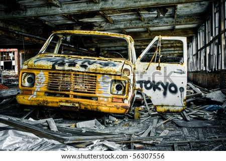 Image of a destroyed old, rusty truck covered in graffiti in an abandoned factory warehouse. - stock photo