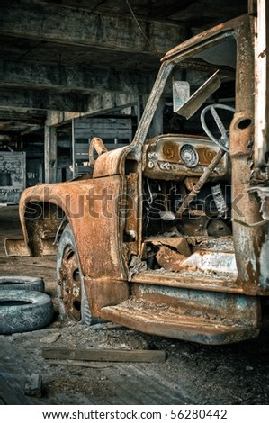 Image of a destroyed old, rusty truck in an abandoned factory warehouse. - stock photo