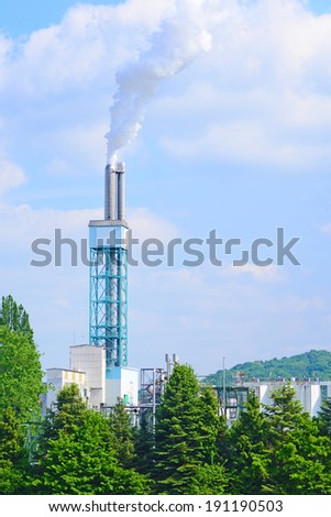 Image of a factory chimney pumping fumes or vapour high into the sky - stock photo