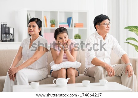 Image of a family where parents are in conflict while their daughter is boring and upset on the foreground  - stock photo