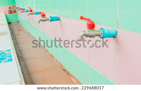 image of a faucet on a tile wall background - stock photo