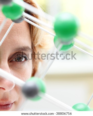 Image of a female researcher eye through a molecular model structure.Selective focus on the eye. - stock photo