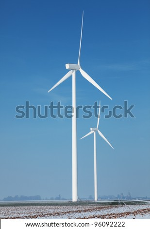 Image of a field with windturbines covered by snow in winter. - stock photo
