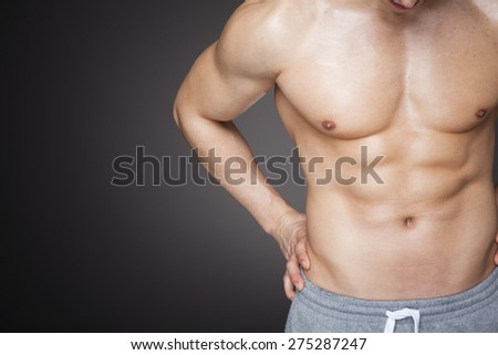 Image of a fit man showing six pack abs against grey background - stock photo