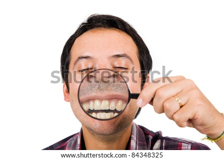 Image of a funny man with magnifying glass held up to face, enlarging mouth and teeth. Isolated - stock photo