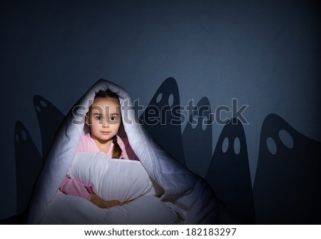 image of a girl under the covers with a flashlight the night afraid of ghosts - stock photo