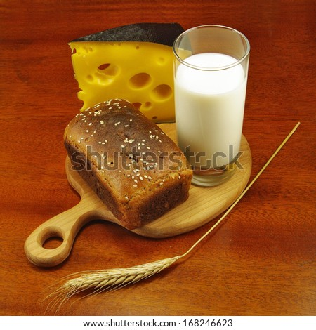 image of a glass of milk, bread on the board, wheat and cheese closeup - stock photo