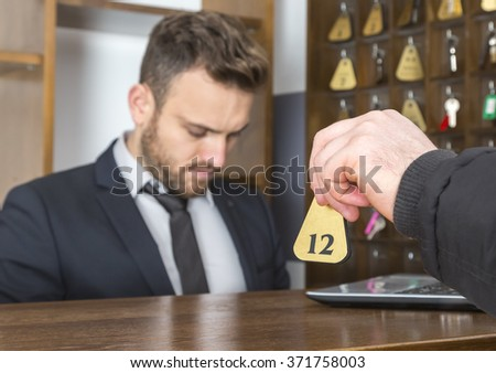 Image of a guest's hand giving the key at the hotel reception. Selective focus on the key. - stock photo