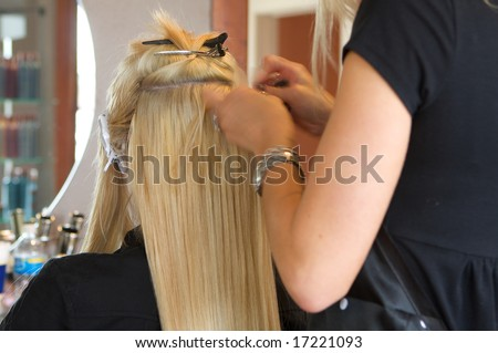 Image of a hairdresser applying extensions to a client's hair - stock photo