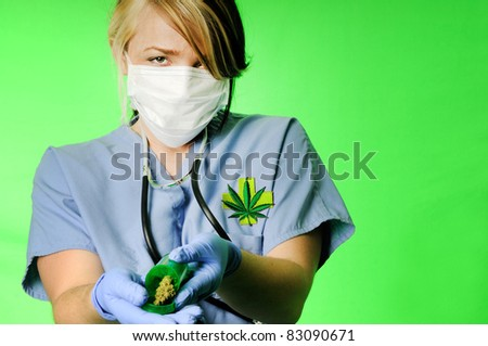 Image of a healthcare professional wearing surgical scrubs, stethoscope and mask holding a prescription bottle with marijuana inside on a chroma key background - stock photo