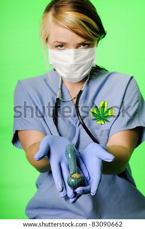 Image of a healthcare professional wearing surgical scrubs, stethoscope and mask presenting a pipe with marijuana on a chroma key background - stock photo