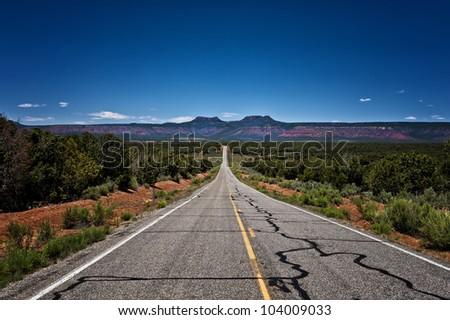 Image of a long desolate road leading off into a plateau - stock photo