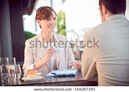 Image of a lovely businesswoman with a teacup on a business lunch with her partner on the foreground  - stock photo