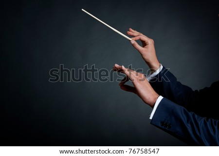 image of a male orchestra conductor directing with his baton in concert - stock photo